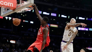 Toronto Raptors' Pascal Siakam, left, dunks past Los Angeles Lakers' Kyle Kuzma (0) during the second half of an NBA basketball game Sunday, Nov. 10, 2019, in Los Angeles. (AP Photo/Marcio Jose Sanchez)