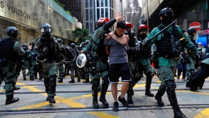 A protester, center, is detained in Central district of Hong Kong on Monday, Nov. 11, 2019. A Hong Kong protester was shot by police Monday in a dramatic scene caught on video as demonstrators blocked train lines and roads during the morning commute. (AP Photo/Vincent Yu)