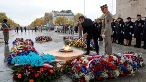 French President Emmanuel Macron lights up the flame at the tomb of the unknown soldier next to French Armies Chief of Staff General Francois Lecointre under the Arc de Triomphe during commemorations marking the 101st anniversary of the 1918 armistice, ending World War I, in Paris Monday Nov. 11, 2019 . (Ludovic Marin/Pool via AP)