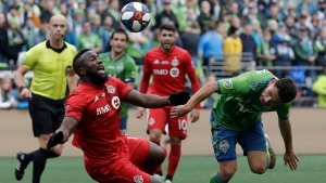 Toronto FC's Jozy Altidore, left, tripped up against Seattle Sounders' Cristian Roldan, Sunday, Nov. 10, 2019, during the second half of the MLS Cup championship soccer match in Seattle. The Sounders won 3-1. (AP Photo/Elaine Thompson)