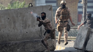 Riot police fire tear gas and smoke bombs during clashes between Iraqi security forces and anti-government protesters in Baghdad, Iraq, Monday, Nov. 11, 2019. (AP Photo/Hadi Mizban)