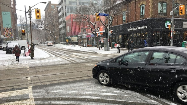 A vehicle navigates snow-co0vered roads in downtown Toronto Monday November 11, 2019. (Joshua Freeman /CP24)