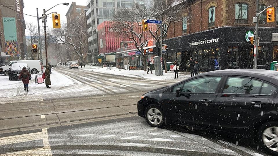 A vehicle navigates snow-covered roads in downtown Toronto Monday November 11, 2019. (Joshua Freeman /CP24)