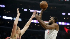 Los Angeles Clippers forward Kawhi Leonard, right, shoots over Toronto Raptors center Marc Gasol during the second half of an NBA basketball game in Los Angeles, Monday, Nov. 11, 2019. (AP Photo/Chris Carlson)