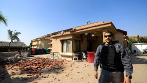 A policeman stands in front of a house hit by a rocket fired from Gaza Strip in Netivot, Israel, after it was hit by a rocket fired from Gaza Strip, Tuesday, Nov. 12m 2019. Israel has killed a senior Islamic Jihad commander in Gaza in a rare targeted killing that threatened to unleash a fierce round of cross-border violence with Palestinian militants. (AP Photo/Tsafrir Abayov)