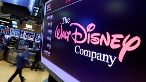FILE - In this Aug. 8, 2017, file photo, The Walt Disney Co. logo appears on a screen above the floor of the New York Stock Exchange. On Tuesday, Nov. 12, Disney Plus launches its streaming service. (AP Photo/Richard Drew, File)