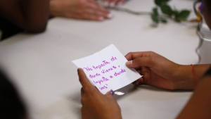 "In this Sept. 24, 2019, photo, a migrant girl in U.S. government custody holds a card that says, in Spanish, ""It doesn't matter where you come from, it matters where you are going,"" during a lesson on reproductive health and self esteem in Lake Worth, Fla. Detention can be traumatic for children, and the nonprofit U.S. Committee for Refugees and Immigrants opened the federally funded Rinconcito del Sol shelter this summer, aiming to make it a model of excellence. Rinconcito del Sol is one of 170 detention centers, residential shelters and foster programs in 23 states which held nearly 70,000 migrant kids in the past year. (AP Photo/Wilfredo Lee)"