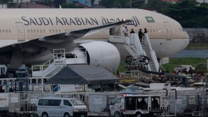 In this file photo, security stand on the stairs of a Saudi Arabian Airlines plane at Manila's International Airport in Pasay, south of Manila, Philippines on Tuesday, Sept. 20, 2016. (AP Photo/Aaron Favila)