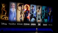 In this April 3, 2019, file photo characters from Disney and Fox movies are displayed behind Cathleen Taff, president of distribution, franchise management, business and audience insight for Walt Disney Studios during the Walt Disney Studios Motion Pictures presentation at CinemaCon 2019. (Photo by Chris Pizzello/Invision/AP, File)