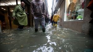 People wade through water on the occasion of a high tide, in a flooded Venice, Italy, Tuesday, Nov. 12, 2019. The high tide reached a peak of 127cm (4.1ft) at 10:35am while an even higher level of 140cm(4.6ft) was predicted for later Tuesday evening. (AP Photo/Luca Bruno)