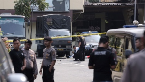 Members of police forensic team inspect the site of a bombing attack at the local police headquarters in Medan, North Sumatra, Indonesia, Wednesday, Nov. 13, 2019. Police say a suicide bomber has blown himself up at a busy police station in Indonesia's third-largest city, injuring a number of people. (AP Photo/Binsar Bakkara)