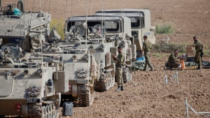 Israeli soldiers prepare their armored vehicles at a gathering point near the border with Gaza on the Israel- Gaza Border, Wednesday, Nov. 13, 2019. Israeli airstrikes killed more Islamic Jihad militants in Gaza on Wednesday as rocket fire toward Israel resumed after a brief overnight lull, raising the death toll in the strip to at least 18 Palestinians in the heaviest round of fighting in months. (AP Photo/Ariel Schalit)