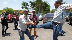 A supporter of Venezuelan President Nicolas Maduro kicks a supporter of Venezuelan opposition leader and self-proclaimed interim president Juan Guaido, outside the Venezuelan Embassy, in Brasilia, Brazil, Wednesday, Nov. 13, 2019. A group of people backing Guaido have occupied the nation's embassy in Brasilia. (AP Photo/Beto Barata)