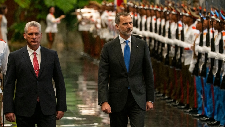 Spain's King Felipe VI, right, and Cuban President Miguel Diaz-Canel review the honor guard at Revolution Palace in Havana, Cuba, Tuesday, Nov. 12, 2019. The Spanish kings are in Havana on an official visit. (AP Photo/Ramon Espinosa)