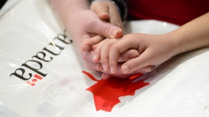 A mother holds the hands of her daughter as they become new Canadians and take the Oath of Citizenship on Parliament Hill in Ottawa on April 17, 2019. New research from Statistics Canada shows a decline in citizenship rates among recent immigrants, especially among those with lower incomes. THE CANADIAN PRESS/Sean Kilpatrick