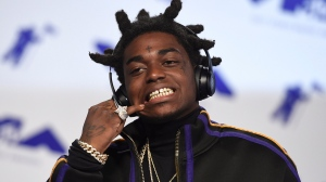 FILE - In this Aug. 27, 2017 file photo, Kodak Black arrives at the MTV Video Music Awards in Inglewood, Calif. The rapper has been sentenced to more than three years in federal prison after pleading guilty to weapons charges stemming from his arrest just before a scheduled concert performance in May. The 22-year-old admitted in August that he falsified information on federal forms to buy four firearms from a Miami-area gun shop on two separate occasions. (Photo by Jordan Strauss/Invision/AP, File)