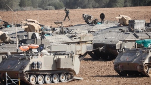 An Israeli soldier walks past military vehicles in a gathering point near the Israel-Gaza Border, Thursday, Nov. 14, 2019. Israel and the militant Islamic Jihad group in Gaza reached a cease-fire on Thursday to end the heaviest Gaza fighting in months. (AP Photo/Ariel Schalit)
