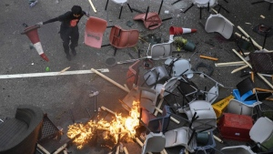 A protester tries remove plastic items from a fire burning amid debris placed to block a road leading to the Cross-Harbour Tunnel in Hong Kong, Thursday, Nov. 14, 2019. University students from mainland China and Taiwan are fleeing Hong Kong, while those from three Scandinavian countries have been moved or urged to leave as college campuses become the latest battleground in the city's 5-month-long anti-government unrest. (AP Photo/Ng Han Guan)