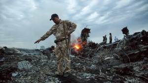 In this July 17, 2014. file photo, people walk amongst the debris at the crash site of MH17 passenger plane near the village of Grabovo, Ukraine, that left 298 people killed. (AP Photo/Dmitry Lovetsky, File)