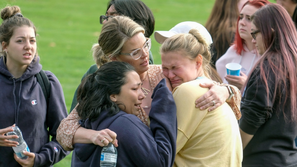 Students are comforted as they wait to be reunited with their parents following a shooting at Saugus High School that injured several people, Thursday, Nov. 14, 2019, in Santa Clarita, Calif. (AP Photo/Ringo H.W. Chiu)