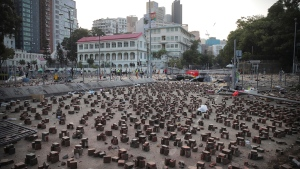 A street is barricaded with bricks near the Hong Kong Polytechnic University in Hong Kong, Friday, Nov. 15, 2019. Protesters who had barricaded themselves in a Hong Kong university this week began to leave Friday after partially clearing a road they had blocked and demanding that the government commit to going ahead with local elections on Nov. 24. (AP Photo/Kin Cheung)