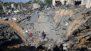 A Palestinian youth stands amid the crater of a destroyed house following overnight Israeli missile strikes, in Al-Qarara, east of Khan Younis, southern Gaza Strip, Thursday, Nov. 14, 2019. (AP Photo/Adel Hana)