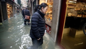 People wade their way through water in Venice, Italy, Friday, Nov. 15, 2019. Waters are rising in Venice where the tide is reaching exceptional levels just three days after the Italian lagoon city experienced its worst flooding in more than 50 years. (AP Photo/Luca Bruno)