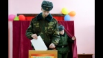 In this photo taken on Thursday, Nov. 14, 2019, a Belarus Army serviceman casts his ballot during an early election at a polling station in Minsk, Belarus, ahead of the parliamentary election to be held on Sunday. (AP Photo/Sergei Grits)
