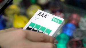 FILE - In this Dec. 20, 2018, file photo a woman buys refills for her Juul at a smoke shop in New York. The e-cigarette maker Juul Labs said Thursday, Nov. 7, 2019, that it will halt sales of its best-selling mint-flavored vaping pods. (AP Photo/Seth Wenig, File)
