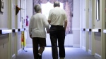 FILE - In this Nov. 6, 2015 file photo, an elderly couple walks down a hall in Easton, Pa. Research released on Friday, Nov. 1, 2019 suggests many American adults inaccurately estimate their chances for developing dementia and do useless things to prevent it. (AP Photo/Matt Rourke, File)