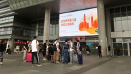 """In this Thursday, Nov. 14, 2019 photo, travelers walk outside the arrival hall at the Shenzhen Bay Port in Shenzhen in southern China's Guangdong Province. Since anti-government demonstrators in Hong Kong began barricading university campuses earlier this week, hundreds of mainland Chinese students have retreated to neighboring Shenzhen, where the ruling Communist Party's Youth League has promised them a """"warm home."""" (AP Photo/Yanan Wang)"""