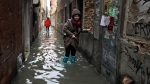 Women wade through water in Venice, on Wednesday, Nov. 13, 2019. On Thursday, the government declared a state of emergency, approving 20 million euros ($22.1 million) to help the historic city repair the most urgent damage. (AP Photo/Luca Bruno)