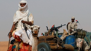 """FILE - In this June 22, 2019 file photo, Gen. Mohammed Hamdan Dagalo, the deputy head of the military council sits on his vehicle surrounded by soldiers from the Rapid Support Forces, RSF, unit during a military-backed tribal rally, in the East Nile province, Sudan. On Wednesday, Oct. 30, 2019, Sudanese officials said Sudan has drawn down its forces taking part in a Saudi-led coalition at war with Yemen's rebels. They declined to disclose how many troops have left Yemen and how many remain, but say """"several thousand troops,"""" mainly from the paramilitary RSF, headed by Dagalo, have returned over the past two months. (AP Photo/Hussein Malla, File)"""