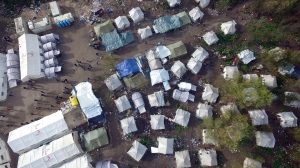 """This aerial photo shows the Vucjak refugee camp outside Bihac, northwestern Bosnia, Friday, Nov. 15, 2019. The European Union's top migration official has joined the calls for the closure of a migrant camp in Bosnia set up on a former landfill. The EU has given Bosnia over 36 million euros ($40 million) in aid. But conditions at Vucjak are so bad that the EU's migration commissioner says that """"no EU financial support can, or will be, provided for it."""" (AP Photo/Eldar Emric)"""