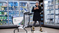 Gina Kaslauskas does her shopping using a new smart cart, part of a pilot project, at a Sobeys grocery store in Oakville, Ont., on Tuesday, November 12, 2019. Shoppers pushing one of 10 new smart carts at a Toronto Sobeys Inc. store can skip the cashier or self-checkout as their carts scan any items put into them, track their total bill and accept payment. THE CANADIAN PRESS/Nathan Denette