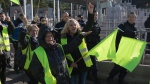 Yellow vest protesters chant as they are escorted by police after they blocked a toll lane during a yellow vest demonstration at the l'Étoile road toll lanes marking the one year anniversary of the yellow vest movement near Marseille, southern France, Saturday, Nov. 17, 2019. Some protests have clashed with police as yellow vest protesters are marking a year of protests, seeking what they see as economic justice for the French people with changes in government policies. (AP Photo/Daniel Cole)