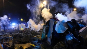 Protestors react as police fire tear gas near Hong Kong Polytechnic University after police gave protestors an ultimatum to leave the campus in Hong Kong, Sunday, Nov. 17, 2019. (AP Photo/Vincent Yu)