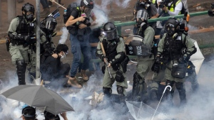 Riot police detain protesters amid clouds of tear gas at the Hong Kong Polytechnic University in Hong Kong, Monday, Nov. 18, 2019. (AP Photo/Ng Han Guan)