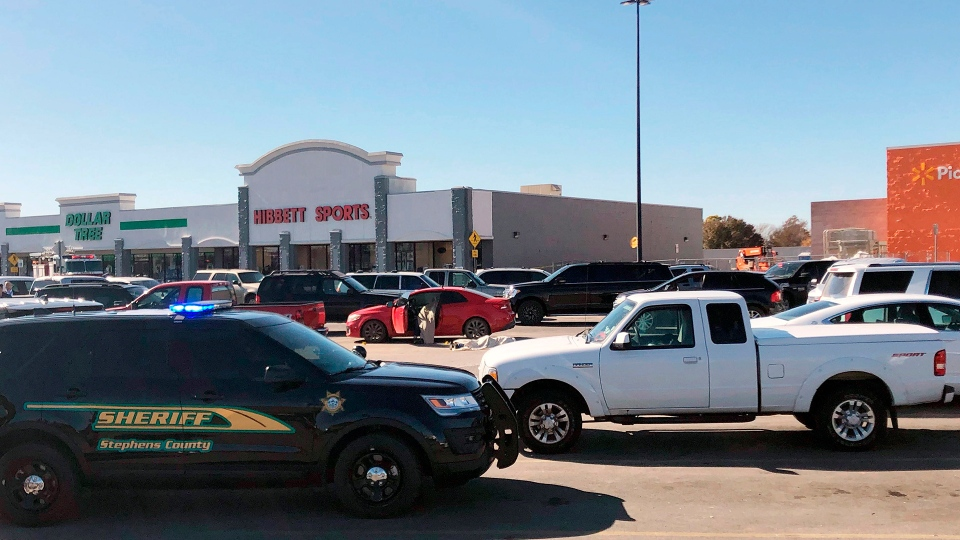 Law enforcement work the scene where two men and a woman were fatally shot Monday, Nov. 18, 2019, outside a Walmart store in Duncan, Okla. Two victims were shot inside a car and the third was in the parking lot outside the store in Duncan, Police Chief Danny Ford said. (AP Photo/Sean Murphy)