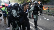 In this Monday, Nov. 18, 2019, photo, riot police detain a protester at Hong Kong Polytechnic University in Hong Kong. About 100 anti-government protesters remained holed up at the university Tuesday as a police siege of the campus entered its third day. (AP Photo/Achmad Ibrahim)