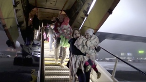 A photo taken from video shows Russian officials carrying children from a plane at Zhukovsky International Airport outside Moscow on Monday night.(Russian Ministry for Emergency Situations via Associated Press)