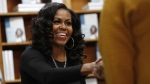 "Former first lady Michelle Obama greets people as they buy signed copies of her book, ""Becoming,"" Monday Nov. 18, 2019, at Politics and Prose Bookstore in Washington. (AP Photo/Jacquelyn Martin)"