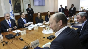Israeli Prime Minister Benjamin Netanyahu, left, looks across the table at his new Defence Minister Naftali Bennett, second right front, at the start of the the weekly cabinet meeting at hthe prime minister's Jerusalem office, Sunday, Nov. 17, 2019. (Gali Tibbon/Pool via AP)