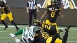 Saskatchewan Roughriders quarterback Zach Collar is hit late by Hamilton Tiger-Cats' Simoni Lawrence after Collaros was downed by Tiger-Cats' Julian Howsare during first half CFL football game action in Hamilton on June 13, 2019.  THE CANADIAN PRESS/Peter Power