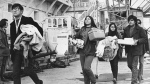 In this Dec. 2, 1969, file photo, a new group of arrivals walks across the docking area with handfuls of possessions during the Native American occupation of Alcatraz Island in San Francisco. The week of Nov. 18, 2019, marks 50 years since the beginning of a months-long Native American occupation at Alcatraz Island in the San Francisco Bay. The demonstration by dozens of tribal members had lasting effects for tribes, raising awareness of life on and off reservations, galvanizing activists and spurring a shift in federal policy toward self-determination. (AP Photo/RWK, File)