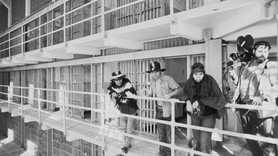 In this Nov. 19, 1969, file photo, part of a band of Native Americans look over the main cell block of Alcatraz after occupying the island in San Francisco. The week of Nov. 18, 2019, marks 50 years since the beginning of a months-long Native American occupation at Alcatraz Island in the San Francisco Bay. The demonstration by dozens of tribal members had lasting effects for tribes, raising awareness of life on and off reservations, galvanizing activists and spurring a shift in federal policy toward self-determination. (AP Photo/RWK, File)