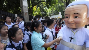 School children greet a man wearing a giant mask of Pope Francis outside Apostolic Nunciature Embassy of the Holy See in Bangkok, Thailand, Wednesday, Nov. 20, 2019. Pope Francis arrived in Bangkok on Wednesday to begin a tour of Thailand and Japan, part of a mission to boost the morale of those countries' tiny minority Catholic communities and speak about issues of concern including human trafficking and peacemaking. (AP Photo/Manish Swarup)