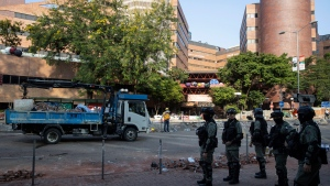 Police officers watch as workers clear the road in front of the Polytechnic University in Hong Kong on Wednesday, Nov. 20, 2019. A small group of protesters refused to leave Hong Kong Polytechnic University, the remnants of hundreds who took over the campus for several days. They won't leave because they would face arrest. Police have set up a cordon around the area to prevent anyone from escaping. (AP Photo/Ng Han Guan)