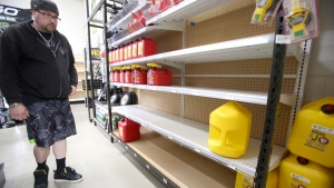 Grass Valley's Dionicio Torres looks at the gas can selection before taking the last 5-gallon gas can on the shelves at B&C Ace Home & Garden Center, Tuesday, Nov. 19, 2019, in preparation of Wednesday's planned public safety power shutdown. (Elias Funez/The Union via AP)