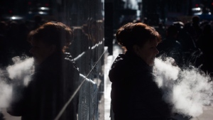 A woman exhales while smoking a vaporizer outside an office tower in downtown Vancouver, Tuesday, Feb. 28, 2017. THE CANADIAN PRESS/Darryl Dyck
